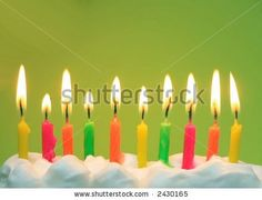 10 lit birthday candles in bright colors with green background - stock photo