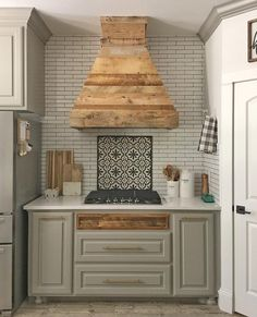 beautiful taupe kitchen cabinets with a rustic wood range vent hood