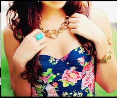 Aqua blue jewelry, gold watch, curly hair and floral dark top