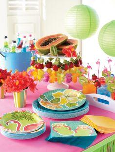 Mira qué bonita combinación de colores para fiesta hawaiana. Mantel rosa, farolillos de papel verdes, jarras azules y menaje con motivos hawaianos. #ideasparafiestas #fiestahawaiana #fiestastematicas