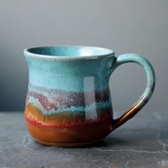 Handmade in Colorado by potter Alan Yarmark, this stoneware mug features brilliant shades of azure blue, rusty oranges, and hints of reds and purples, made even more spectacular when finished with a glossy glaze. Sits comfortably in your hand and is functional for everyday use