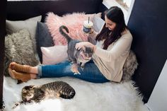 A customer pets cats while drinking coffee at the flagship Washington, D.C. location of cat cafe Crumbs & Whiskers.