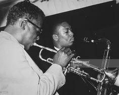 American jazz trumpeter Miles Davis (1926-1991) performs with tenor saxophonist John Coltrane (1926-1967). Coltrane played in Davis' Sextet that year. Davis wears dark sunglasses.