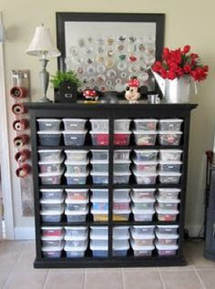 Go buy a banged up dresser from the thrift store. Ditch the drawers, sand it and paint it, and you have a set of shelves to house plastic tubs!