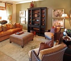 Toned down burt orange color scheme looks amazing in this living room. Mixed with the taupe and chocolate brown, it's warm, and inviting and cheerful.