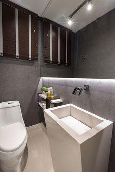 Lavabo com cuba esculpida apoiada no piso, paredes revestidas com papel de parede e estrutura em ferro com pranchas em laca para apoio.