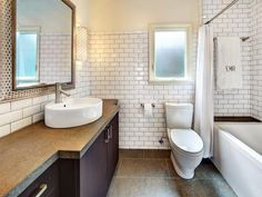 White subway tile with dark grout.  Provides a somewhat more traditional look - AND less drama trying to keep the grout clean?