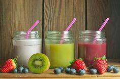 Three flavored smoothies in jars including kiwi blueberry and strawberry
