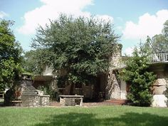 overgrown tree hides the back, but you can see the outside fireplace / kitchen area