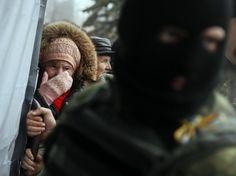 A woman cries as she waits for humanitarian aid near a Ukrainian serviceman stands nearby in Debaltseve, eastern Ukraine, February 6, 2015. REUTERS/Gleb Garanich