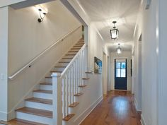Hickory-wood floors are both beautiful and durable for this high-traffic area. The entry's pairing of modern with traditional hints at the home's overall design scheme. White Stair Risers, White Banister, Love Your Home, My Dream Home, Hickory Wood Floors, Wood Flooring, Wood Staircase, Hardwood Stairs, Staircases