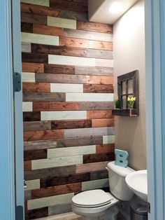 Multi colored ship lap bathroom wall. Wood purchased at Lowe's and cut to different sizes across the width of the wall. Painted/stained the wood different colors.