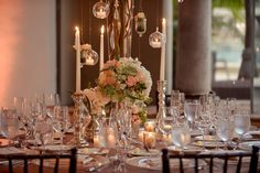 Gorgeous peach, pink and green floral centerpiece wedding table. Love the hanging votive candles!