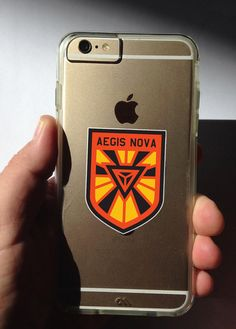 This listing is for one high quality vinyl Ingress Themed Aegis Nova Anomaly sticker, for your cellphone, laptop, charger, car, truck, bike, minivan, mirror, window, binder, cat, dog, or whatever needs stickering.  Stickers are offered in two sizes: Small (approximately 1.5 x 2) and Large (approximately 3 x 4) in stunning full color as seen in the photograph.  These vinyl stickers are long lasting, color-fast, weather durable, look great on a variety of surfaces, and are easy to remove. This…