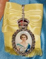 The Royal Order of Sartorial Splendor of Elizabeth II is a portrait of herself painted on ivory in a diamond frame topped by a Tudor crown and set on a pale yellow silk bow with her cypher on the back side.  It is a private award and the only way to know a person has received it is it is worn in public.