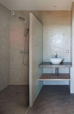 béton ciré du sol aux murs, cette salle de bains propose une douche épurée