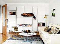 .white walls, white modern storage, white sofa, white coffee table, black & white rug. monochromatic works
