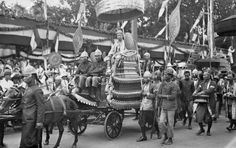 H.M. King Monivong - being paraded through the streets on a gold chariot drawn by five horses following his second coronation ceremony in Phnompenh.