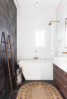 This renovated home is a tropical resort-style haven Dark limestone tiles line the wall and floor of this bathroom space. A generous freestanding bath tub sits at the end and a walk-in shower features brass tapware and fixtures. Shower Bath Combo, Shower Over Bath, Shower Tub, Freestanding Tub With Shower, Shower Tiles, Upstairs Bathrooms, Small Bathroom, Modern Bathroom, Bathroom Marble