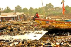A boy sits on a boat in the harbor of Kroo Bay in Freetown, Sierra Leone. It is estimated that 55,000 people live here. . .it is the city's garbage dump.