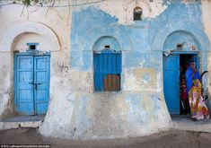 Stunning: A colourfully dressed woman and children emerge from a house that dates back to the Ottoman Empire in Somaliland's port city of Berbera ▼2Apr2014MailOnline|Sun, sea, sand and some VERY scary locals! On the tourist trail in war-torn Somalia's breakaway Somaliland region http://dailym.ai/1opgyQD #Somaliland #Soomaaliland