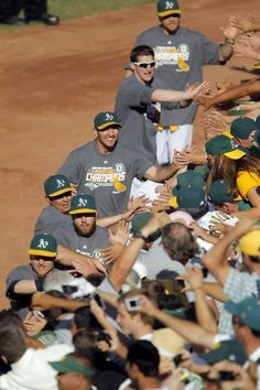 A's players high five fans after they defeated the Texas Rangers. The Oakland Athletics won the American League West division after they defeated the Texas Rangers at O.co Coliseum in Oakland, Calif., on Wednesday, October 3, 2012. Photo: Carlos Avila Gonzalez, The Chronicle / SF