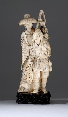 """IVORY OKIMONO Meiji Period Two highly decorated figures with detailed robes and carrying a variety of baskets containing flowers and fruit. Signed """"Naomasa"""". Height 9.75 (24.76 cm)."""
