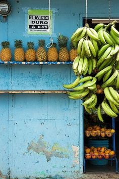 Pineapples and bananas in a tropical market. Shop the Matthew Williamson beachwear collection on our online boutique.