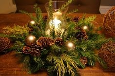 Do something like this centerpiece but put a figurine or ornament in the hurricane lamp instead of a candle.  Then put other figurines and by theresa