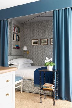 "Bed curtains and a pocket of patterned wallpaper give the feeling of a cosy room-within-a-room in a small bedroom at a [link url=""http://www.houseandgarden.co.uk/interiors/real-homes/veere-grenney""]modern country home designed by Veere Greeney[/link]. The bed curtains are in a wool felt from Holland"