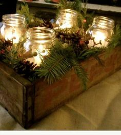 Christmas centerpiece made with an old crate, mason jars, greens and berries. Love the simplicity and natural look.