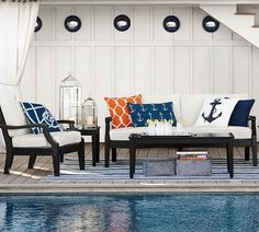 Orange and navy pillows give this coastal patio a dash of preppy.