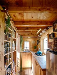 Every inch of wall space is utilized to keep the Tiny Tack House kitchen in order. Mugs and pans hang high above the stove, shallow shelves create a tidy pantry, and hanging baskets act as extra shelves.   Photo: Christopher Tack