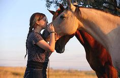 Animals are increasingly being used in therapy. Here, the daughter of NASW member Mike Gooch, stands with Moon, a horse at Home on the Range, a therapeutic equine program Mike founded in North Dakota.