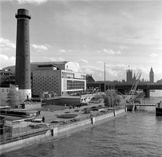 The Royal Festival Hall looking south from Waterloo Bridge, was designed by Sir Robert Matthew and J L Martin. It was built in 1949-51 as a concert hall for the Festival of Britain. The Shot Tower, which is still standing here, was demolished after the Festival of Britain to build the Queen Elizabeth Hall.