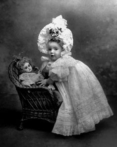 Portrait of young girl posing with her bebe Jumeau doll, c. 1900