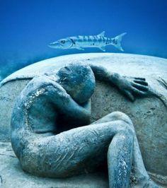 La sculpture d'un homme allongé sur le pare-brise d'une voiture, plongée dans un milieu sous-marin