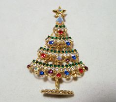 Vintage Christmas tree brooch •Multi color glass rhinestones, gold tone swags, topped with a star •Layered open work setting •Free standing,