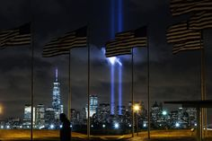 A man walks past as the Tribute in Light is illuminated on the skyline of lower Manhattan during events marking the 13th anniversary of the 9/11 attacks on the World Trade Center in New York, September 10, 2014. REUTERS/Eduardo Munoz