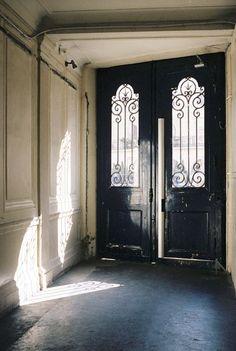 Black doors. Black doors with iron scrolling. Dark floors.