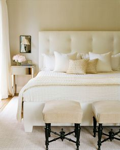 Two ottomans stand at the foot of an all-white upholstered bed.