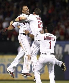 Texas Rangers' Nelson Cruz, left, celebrates with teammates Craig Gentry (23) and Elvis Andrus (1) after Cruz's game-winning RBI double in the 10th inning of a baseball game against the Minnesota Twins on Saturday, July 7, 2012, in Arlington, Texas. Adrian Beltre scored the winning run for the 4-3 victory. (AP Photo/LM Otero)  game 85