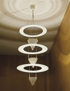'SATELLITE' CEILING LIGHT, by EILEEN GRAY, circa 1925 In cream-painted aluminium, composed of three superimposed flat rings in ascending scale mounted in alternation with three stepped conical shades in descending scale Hauteur : 135 cm Diamètre : 48 cm Eileen Gray, Lamp Design, Lighting Design, Lighting Ideas, Bauhaus, Harlem Renaissance, Interior Design History, Stairway Lighting, Arquitetura