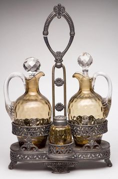 INVERTED THUMBPRINT THREE-PIECE CASTER SET, light amber, comprising two cruets with applied colorless handles and facetted stoppers, and a single barrel shaker with two-part lid. Fitted in a quadruple-plate four-section stand marked for Simpson, Hall, Miller & Co. and numbered 53. Fourth quarter 19th century.