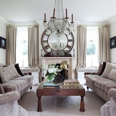 Elegant sitting room  Striking antique objects make a statement in this neutral living room. The fireplace, large mirror and impressive chandelier are a stunning focal point.