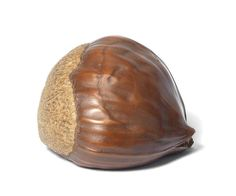 A wood netsuke of a chestnut By Morita Soko (1879-1942), Tokyo, 20th century Naturalistically carved, the roughened end contrasting with the smooth polished surface of the skin, and stained for effect, signed Soko to.