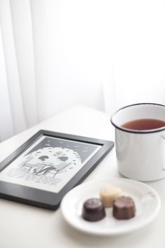 Foto clean em tons claros e bem iluminada com clima aconchegante de outono/inverno. Caneca zezé branca com chá em cima de uma mesa de cabeceira em composição com um kobo (e-reader) com o livro Soppy aberto e um pratinho com chocolates belga.