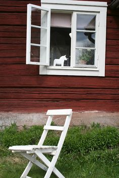 a white dala horse in the windoe of a red wooden house - nordingården