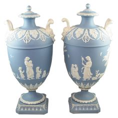 """A rare pair of Wedgwood blue and white jasper two handled covered vases decorated in relief with """"Lady Templetown"""" designs, upper case marks"""