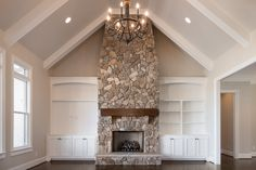 The perfect fireplace. Floor to ceiling stonework, farmhouse style mantle, custom white built ins on either side and the perfect chandelier on a vaulted ceiling.  This gorgeous home in Greenville, SC is for sale! See and read more here - http://www.goodwinfoust.com/homesforsale/